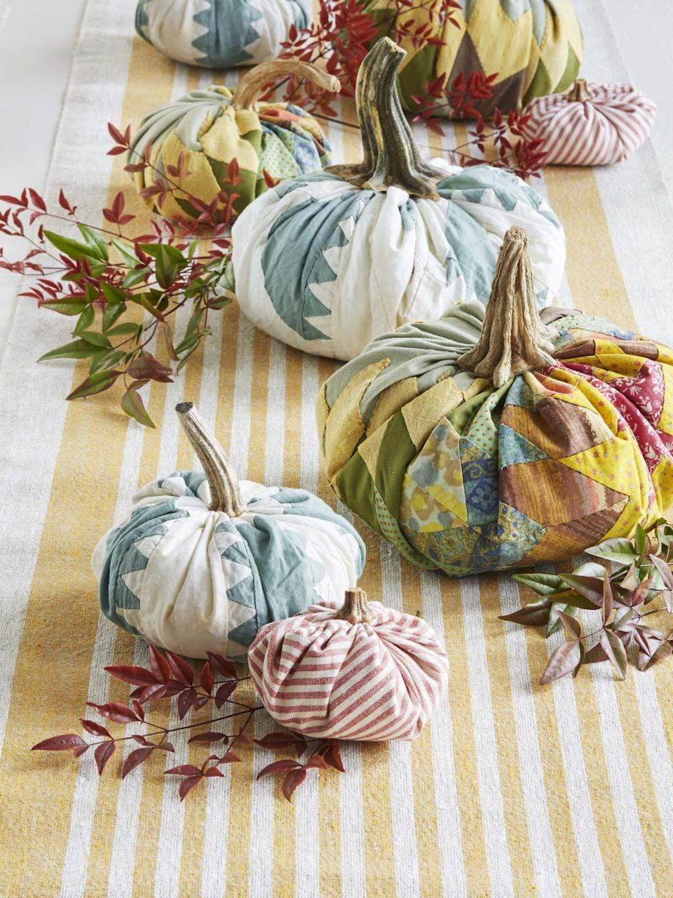 """<p>Craft your own personal pumpkin patch using old quilts and fabric scraps. <strong><br></strong></p><p><strong>To make:</strong> Start with a round piece of fabric and a ball of batting (about the size you want your finished pumpkin to be). Gather the fabric up around the batting and hot glue it together in the center. Collect dried stems, or purchase faux stems, and attach with hot glue for a realistic touch. Line the middle of a long farmhouse table with a runner, then pile on your creations and other seasonal greenery. These would be an adorable accent to a mantel or buffet as well.</p><p><a class=""""link rapid-noclick-resp"""" href=""""https://www.amazon.com/s?k=pumpkin+stems&i=handmade&ref=nb_sb_noss_2&tag=syn-yahoo-20&ascsubtag=%5Bartid%7C10050.g.2063%5Bsrc%7Cyahoo-us"""" rel=""""nofollow noopener"""" target=""""_blank"""" data-ylk=""""slk:SHOP FAUX PUMPKIN STEMS"""">SHOP FAUX PUMPKIN STEMS</a></p>"""