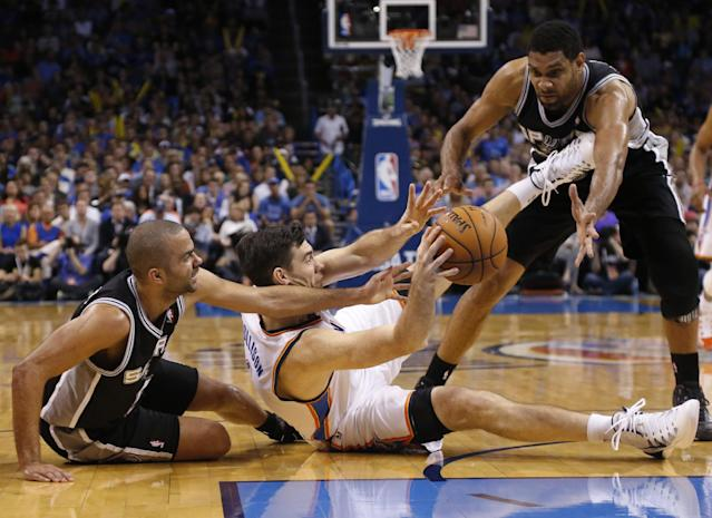 Oklahoma City Thunder forward Nick Collison (4) passes from between San Antonio Spurs guard Tony Parker, left, and forward Tim Duncan during the third quarter of an NBA basketball game in Oklahoma City, Thursday, April 3, 2014. Oklahoma City won 106-94. (AP Photo/Sue Ogrocki)