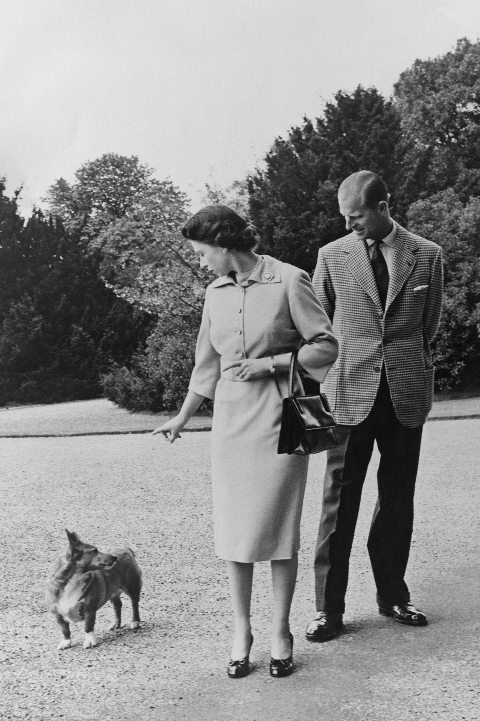 <p>Queen Elizabeth and Prince Philip take their corgi, Sugar, for a walk outside the George IV gateway at Windsor Castle in the Summer of 1959.</p>