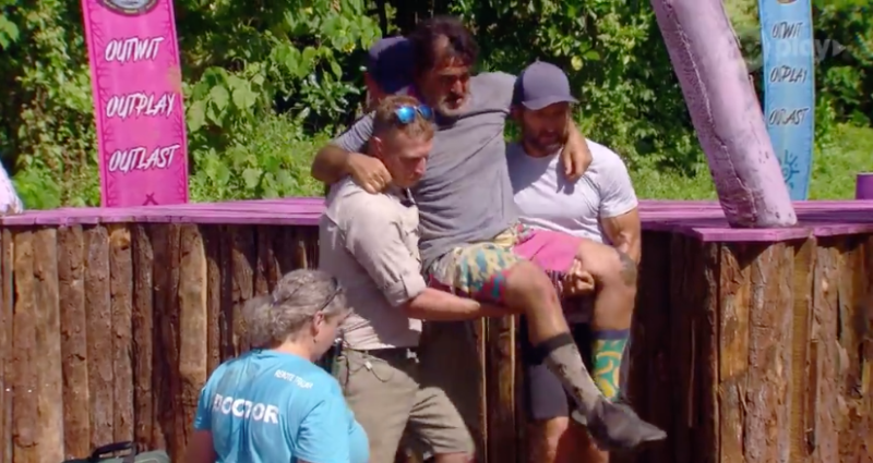 A photo of Australian Survivor contestant Ross Clarke-Jones being carried off set by host Jonathan LaPaglia after breaking his ankle.