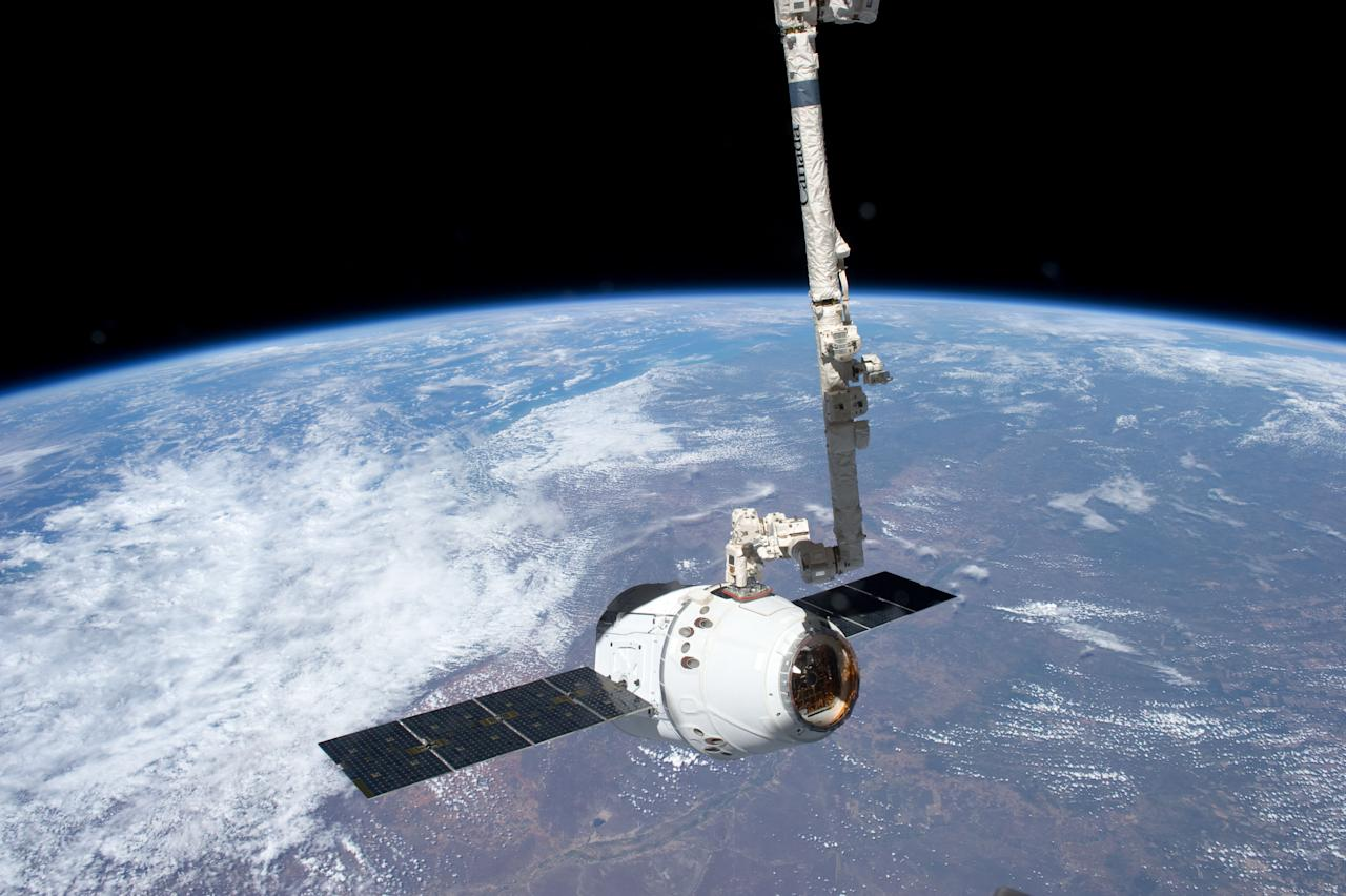 In this image provided by NASA, the SpaceX Dragon commercial cargo craft is grappled by the Canadarm2 robotic arm at the International Space Station Friday May 25, 2012. Expedition 31 Flight Engineers Don Pettit and Andre Kuipers grappled Dragon at 9:56 a.m. (EDT) and used the robotic arm to berth Dragon to the Earth-facing side of the station's Harmony node at 12:02 p.m. May 25, 2012. Dragon became the first commercially developed space vehicle to be launched to the station. Dragon is scheduled to spend about a week docked with the station before returning to Earth on May 31 for retrieval. (AP Photo/NASA)