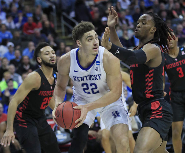 <p>Kentucky's Reid Travis (22) looks to pass around Houston's Galen Robinson Jr., left, and Cedrick Alley Jr., right, during the first half of a men's NCAA tournament college basketball Midwest Regional semifinal game Friday, March 29, 2019, in Kansas City, Mo. (AP Photo/Orlin Wagner) </p>