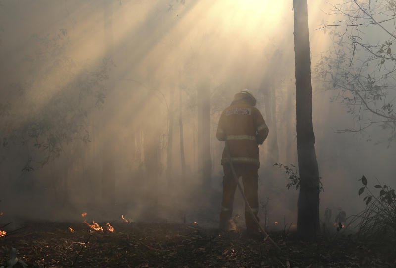 A firefighter mops up after a firestorm swept through a property in Bilpin, 75 kilometers (47 miles) from Sydney, Wednesday, Oct. 23, 2013. Scores of Australians evacuated their homes in mountains west of Sydney on Wednesday as intensifying winds fanned wildfires and grounded the helicopters that were fighting them. (AP Photo/Rob Griffith)