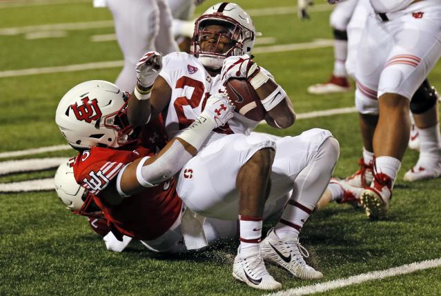 """Utah linebacker Kavika Luafatasaga, left, tackles Stanford running back <a class=""""link rapid-noclick-resp"""" href=""""/ncaaf/players/257525/"""" data-ylk=""""slk:Bryce Love"""">Bryce Love</a> (20) in the first half during an NCAA college football game Saturday, Oct. 7, 2017, in Salt Lake City. (AP Photo/Rick Bowmer)"""