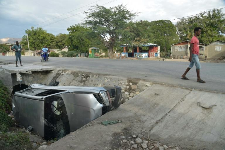 A car damaged by a bus lies on the side of a road in Gonaives