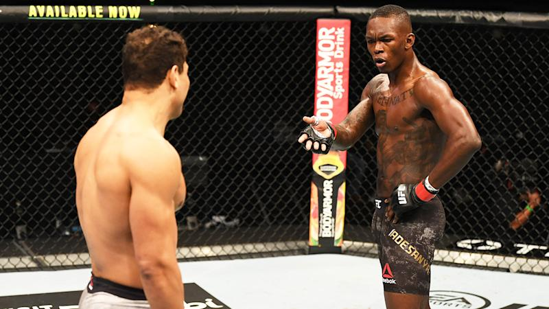 Israel Adesanya looks and gestures to Paulo Costa in their middleweight championship bout.