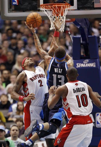Dallas Mavericks guard Delonte West (13) goes for a layup between Toronto Raptors forward James Johnson (2) and DeMar DeRozan (10) during the first half of an NBA basketball game in Dallas on Friday Dec. 30, 2011. (AP Photo/Mike Fuentes)