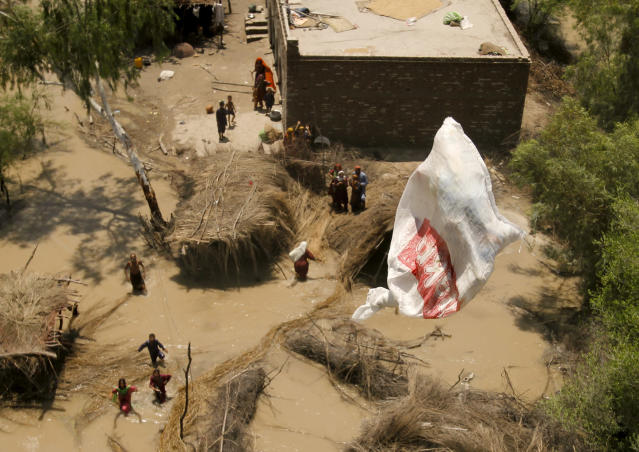 <p>Pakistani villagers chase relief supplies dropped from a Pakistani navy helicopter at a flooded area of Ghaus Pur near Sukkur, in Pakistan's Sindh province, Aug. 11, 2010. (AP Photo/Shakil Adil) </p>