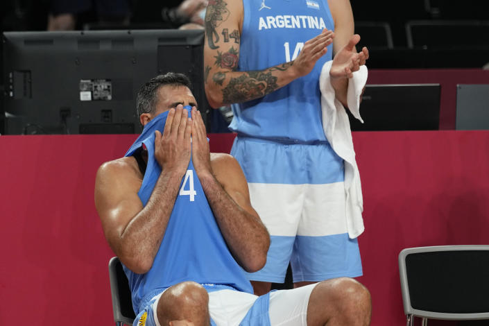 Argentina's Luis Scola (4) pulls his jersey over his face as he receives an emotional standing ovation from his team, Australia players, and others in attendance when he was pulled from the game in the final moments of a men's basketball quarterfinal round game at the 2020 Summer Olympics, Tuesday, Aug. 3, 2021, in Saitama, Japan. (AP Photo/Eric Gay)