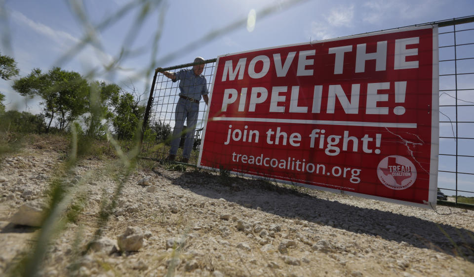 Andy Sansom closes the gate to his property where a proposed new natural gas pipeline would pass through his ranch in the Texas Hill Country near Stonewall, Texas Friday, Aug. 2, 2019. A proposed pipeline is a 430-mile, $2 billion natural gas expressway that pipeline giant Kinder Morgan has mapped from the booming West Texas oil patch to Houston. (AP Photo/Eric Gay)