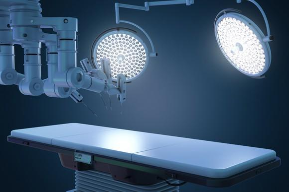 Robotic surgery setup with an operating table and bright lights.