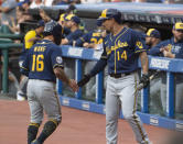 Milwaukee Brewers' Jace Peterson (14) congratulates Kolten Wong for scoring on a triple by Christian Yelich during the first inning of a baseball game against the Cleveland Indians in Cleveland, Saturday, Sept. 11, 2021. (AP Photo/Phil Long)