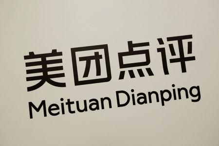 FILE PHOTO: Company logo of China's Meituan Dianping is displayed at a news conference in Hong Kong