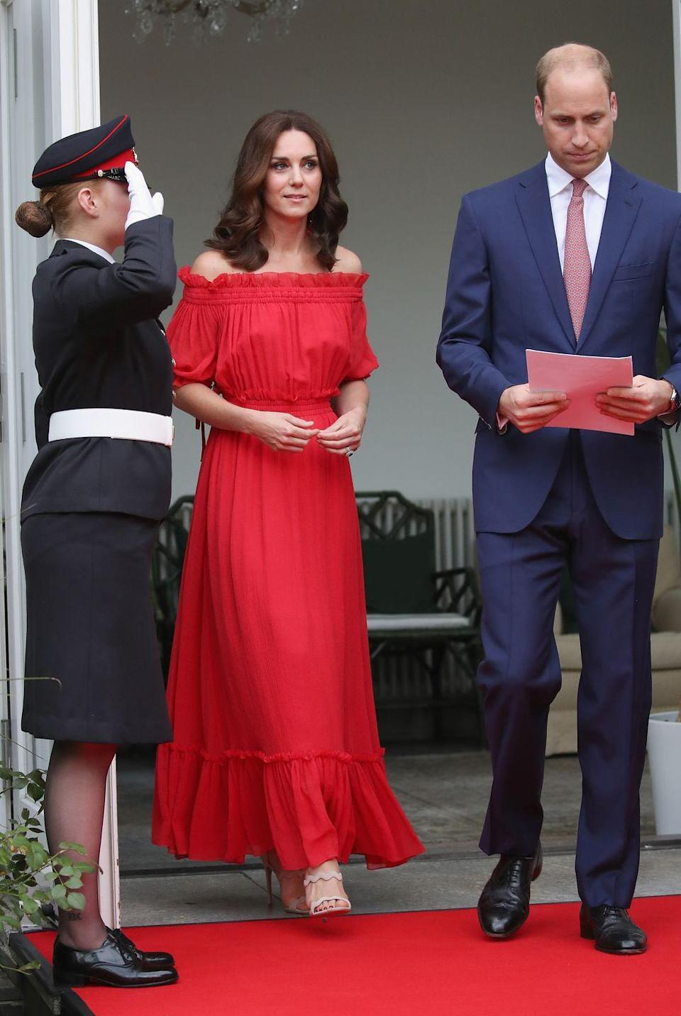 "<p>The Duchess wore a maxi dress by Alexander McQueen <a href=""https://www.townandcountrymag.com/society/tradition/g10295873/kate-william-royal-family-tour-germany-poland-2017/"" rel=""nofollow noopener"" target=""_blank"" data-ylk=""slk:to a garden party held in the Queen's honor"" class=""link rapid-noclick-resp"">to a garden party held in the Queen's honor</a> while in Berlin during the royal tour. She paired the summery dress with scalloped sandals by Prada. </p>"