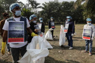 Volunteers wearing face masks as a precaution against the coronavirus clear the debris left over by tourists at Maidan, the city's largest open space in Kolkata, India, Sunday, Jan. 3, 2021. India authorized two COVID-19 vaccines on Sunday, paving the way for a huge inoculation program to stem the coronavirus pandemic in the world's second most populous country. (AP Photo/Bikas Das)
