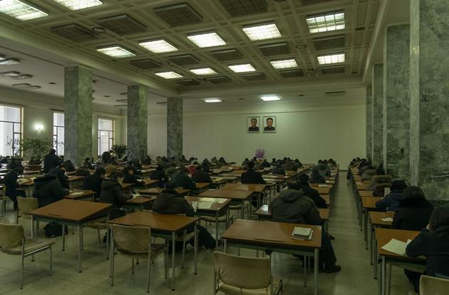 Students study at the Grand People's Study House. The portraits of Kim Il-sung and Kim Jong-il are common in North Korea and can be found in most buildings, including homes.