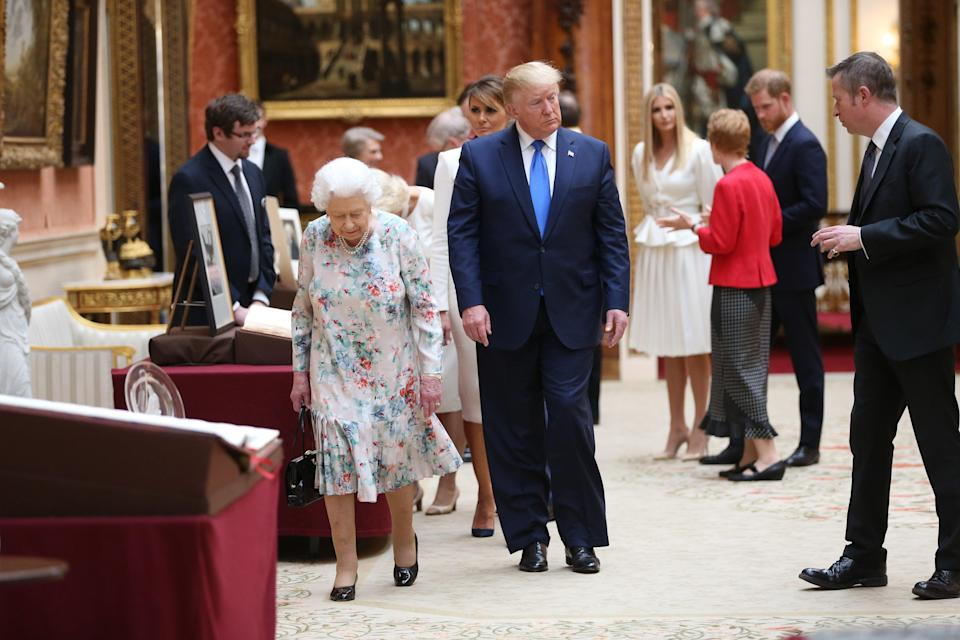 <p> Queen Elizabeth II (L) and US President Donald Trump (2nd L) view American items in the Royal collection while Ivanka Trump (4th R) daughter of US President Donald Trump, speaks with Prince Harry, Duke of Sussex (2nd R) at Buckingham Palace on June 3, 2019 in London, England.</p> (Photo by Ian Vogler - WPA Pool/Getty Images)