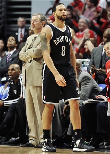 Brooklyn Nets head coach P.J. Carlesimo, rear left, stands on the court as Nets' Deron Williams (8) walks past the bench in the closing seconds during the third overtime in Game 4 of their first-round NBA basketball playoff series against the Chicago Bulls on Saturday, April 27, 2013, in Chicago. The Bulls won 142-134 in three overtimes. (AP Photo/Jim Prisching)