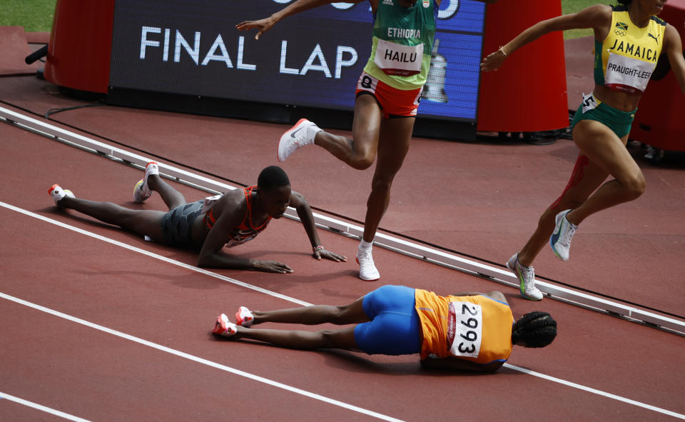 Tokyo 2020 Olympics - Athletics - Women's 1500m - Round 1- OLS - Olympic Stadium, Tokyo, Japan - August 2, 2021. Sifan Hassan of the Netherlands and Edina Jebitok of Kenya fall down during Heat 2 REUTERS/Phil Noble