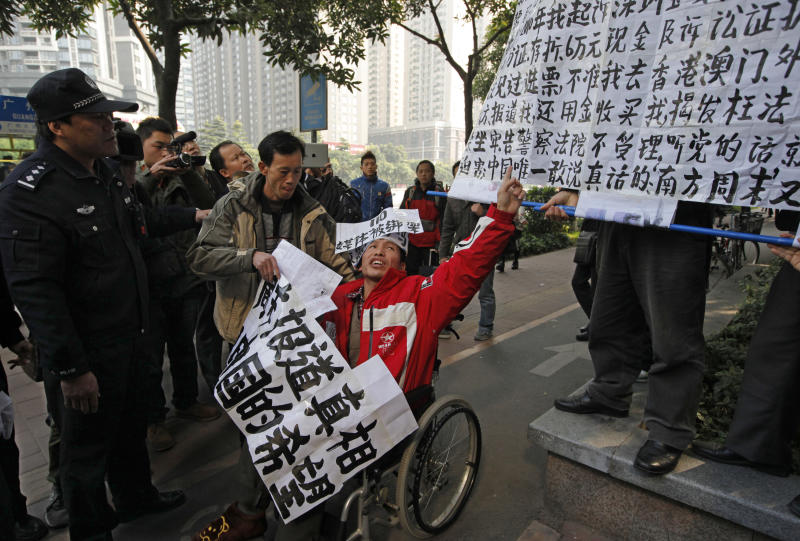 In this Thursday, Jan. 10, 2013 photo, a policeman stands against a supporter in a wheelchair of the Southern Weekly during a protest before being taken away by the police near the Southern Weekly headquarters in Guangzhou, Guangdong province, China. China's new Communist Party leaders want to appear more open, but they're not about to give up control of the media. That's the lesson of a dustup involving the influential newspaper whose staff briefly rebelled against especially heavy-handed censorship. (AP Photo/Vincent Yu)