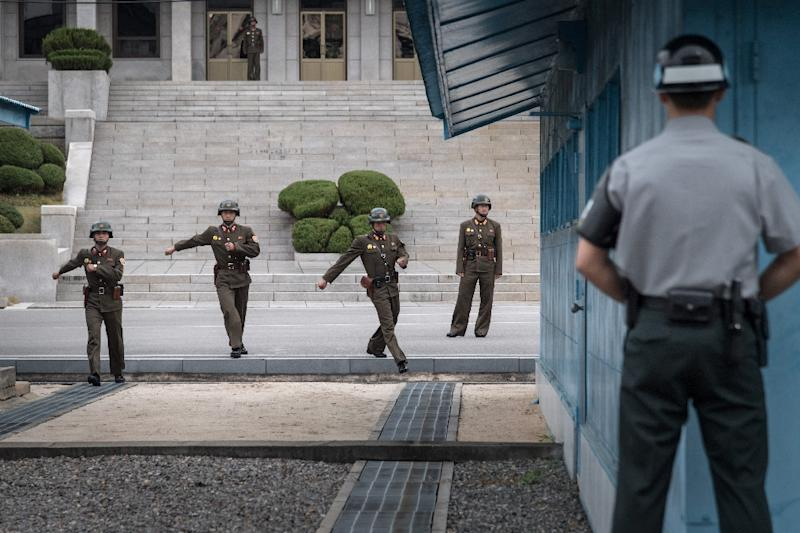 A South Korean soldier (R) watches North Korean soldiers walking towards the military demarcation line separating North and South Korea at the truce village of Panmunjom