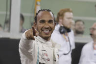 Mercedes driver Lewis Hamilton of Britain celebrates pole position during the qualifying session at the Yas Marina racetrack in Abu Dhabi, United Arab Emirates, Saturday, Nov. 30, 2019. The Emirates Formula One Grand Prix will take place on Sunday. (AP Photo/Hassan Ammar)