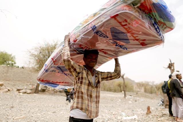 <p>A man displaced from the Red Sea port city of Hodeidah carries mattresses he received from the local Mona Relief charity in Sanaa, Yemen July 18, 2018. (Photo: Khaled Abdullah/Reuters) </p>