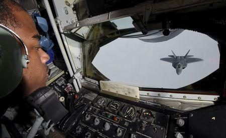 A crew member looks out of a KC-135 refuelling plane as a U.S. F-22 Raptor fighter prepares to connect to a fuel line over European airspace during a flight to Britain from Mihail Kogalniceanu air base in Romania April 25, 2016. REUTERS/Toby Melville
