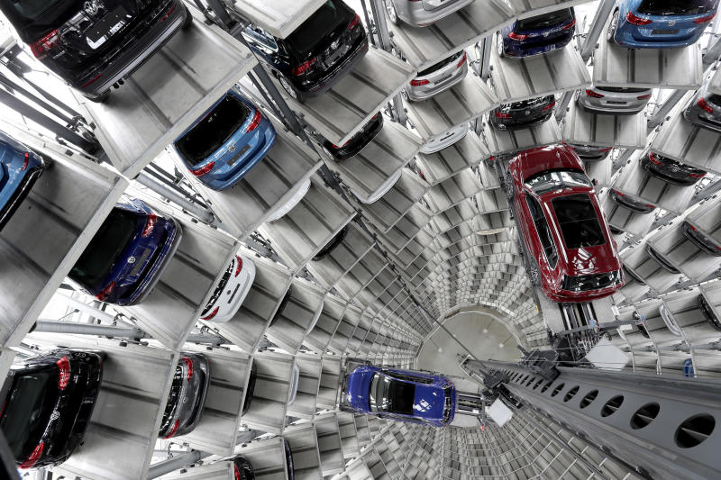 FILE - In this March 14, 2017 file photo Volkswagen cars are lifted inside a delivery tower of the company in Wolfsburg, Germany. German automaker Volkswagen saw operating profit slip in the first quarter 2019 as the company set aside 1 billion euros for legal issues but reaffirmed its profit goals for the year and saw better profits at its core brand. (AP Photo/Michael Sohn, file)