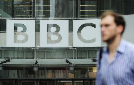 A pedestrian walks past a BBC logo at Broadcasting House in central London