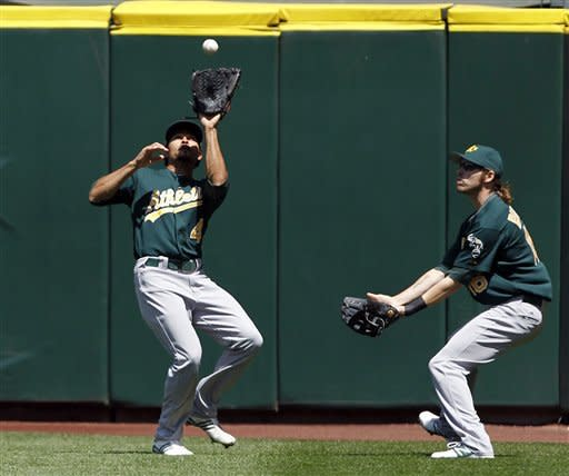Oakland Athletics center fielder Coco Crisp, left, fields a fly ball from Seattle Mariners' Michael Saunders as left fielder Seth Smith moves in in the fourth inning of a baseball game, Wednesday, June 27, 2012, in Seattle. (AP Photo/Elaine Thompson)