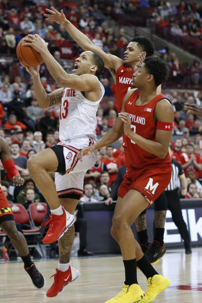 Ohio State's C.J. Walker, left, takes a shot between Maryland's Anthony Cowan, center, and Aaron Wiggins during the second half of an NCAA college basketball game Sunday, Feb. 23, 2020, in Columbus, Ohio. Ohio State defeated Maryland 79-72. (AP Photo/Jay LaPrete)