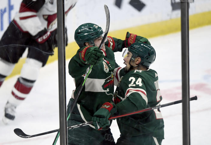 Minnesota Wild's Matt Dumba (24) congratulates teammate Kevin Fiala (22), of Switzerland, on his goal against the Arizona Coyotes during the third period of an NHL hockey game Sunday, March 14, 2021, in St. Paul, Minn. (AP Photo/Hannah Foslien)