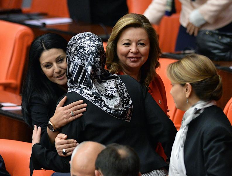 Gulay Samanci, one of four ruling Justice and Development Party lawmakers wearing headscarves, who walked into Turkey's parliament, is congratulated by other lawmakers in Ankara Thursday, Oct. 31, 2013, marking the end of a longstanding ban in the chamber. The female members of parliament had announced their intentions after restrictions that were imposed in the early days of the Turkish Republic were recently lifted. The issue is highly charged in a country founded in 1923 under strict secular principles.(AP Photo)