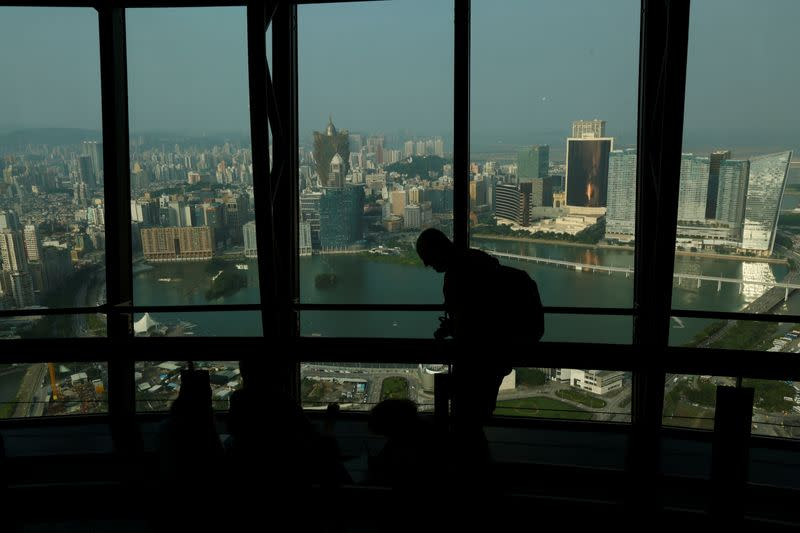 A visitor walks inside Macau Tower overlooking a general view of Macau peninsula