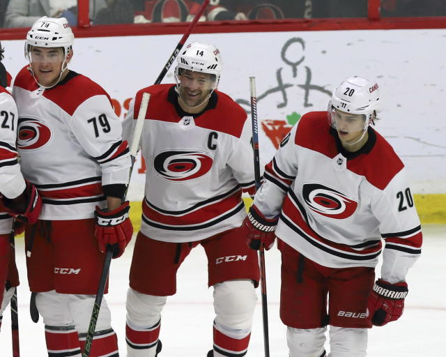 Carolina Hurricanes' Justin Williams (14) celebrates his winning goal against the Ottawa Senators with teammates Michael Ferland (79) and Sebastian Aho (20) during third-period NHL hockey play in Ottawa, Ontario, Sunday, Jan. 6, 2019. (Fred Chartrand/The Canadian Press via AP)