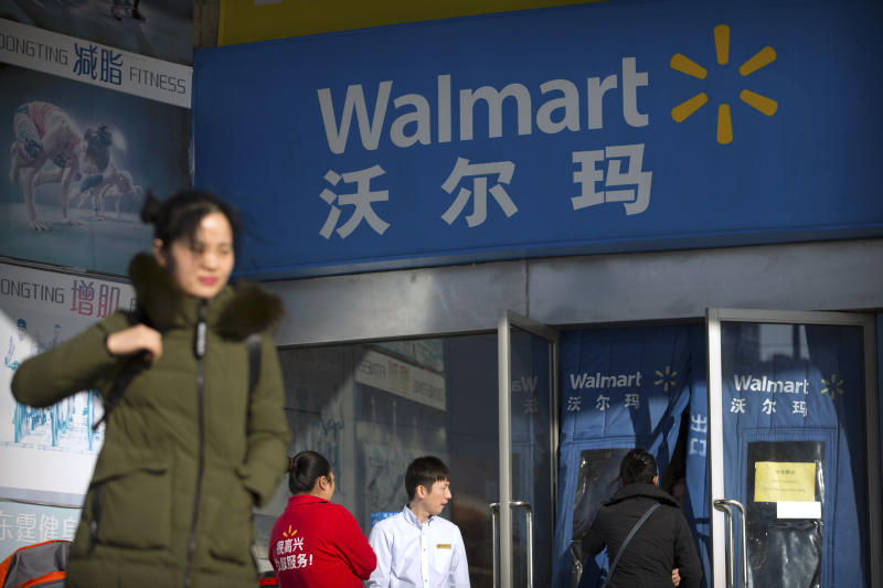 People walk past a Walmart store in Beijing, China, Wednesday, Dec. 6, 2017. (AP Photo/Mark Schiefelbein)