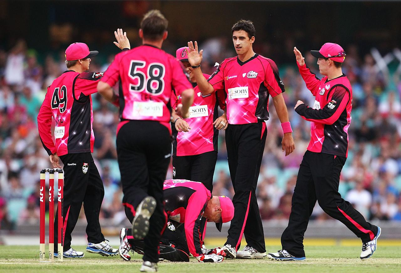 SYDNEY, AUSTRALIA - DECEMBER 08:  Mitchell Starc is congratulated after getting the wicket of Usman Khawaja  during the Big Bash League match between the Sydney Sixers and the Sydney Thunder at Sydney Cricket Ground on December 8, 2012 in Sydney, Australia.  (Photo by Mark Nolan/Getty Images)