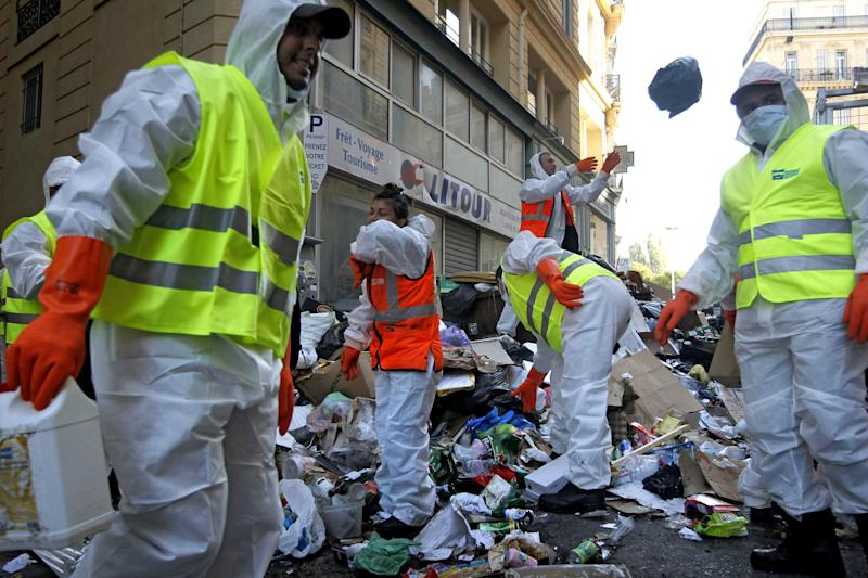 """Garbage collectors began tackling Marseille's reeking mounds of trash in the center of Marseille, southern France, Tuesday, Oct. 26, 2010. Striking garbage collectors in Marseille faced 9,000 tons of garbage that have piled up in the streets in the last two weeks. The FO union voted Monday evening to end the protest out of concerns over """"hygiene and safety."""" City authorities said it would take four to five days before France's second-largest city starts looking, and smelling, like itself. (AP Photo/Laurent Cipriani)"""