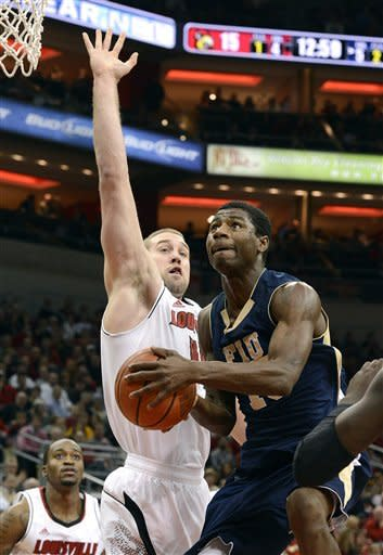 Florida International's Tymell Murphy, right, drives to the basket around the defense of Louisville's Stephan Van Treese during the first half of an NCAA college basketball game on Wednesday, Dec. 19, 2012, in Louisville, Ky. (AP Photo/Timothy D. Easley)