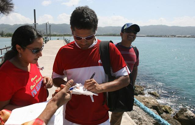 Montego Bay, JAMAICA: Indian Cricketer Sachin Tendulkar gives autographs to Indian fans after teams sightseeing trip in Montego Bay 10 March 2007. The opening ceremony of the World Cup will be held in Trelawny, Jamaica on 11 March. AFP PHOTO/Prakash SINGH (Photo credit should read PRAKASH SINGH/AFP/Getty Images)