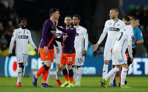 Manchester City's Aymeric Laporte clashes with Swansea City players at half time - Credit: REUTERS