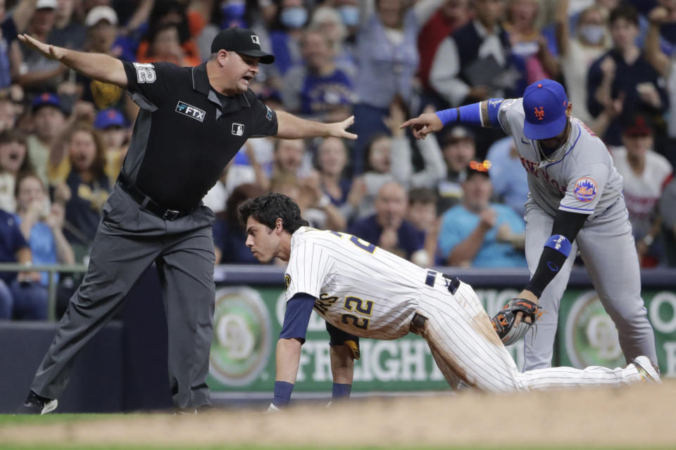 Milwaukee Brewers' Christian Yelich (22) slides safely into third base past the tag of New York Mets' Jonathan Villar, right, for a triple during the fifth inning of a baseball game Friday, Sept. 24, 2021, in Milwaukee. (AP Photo/Aaron Gash)