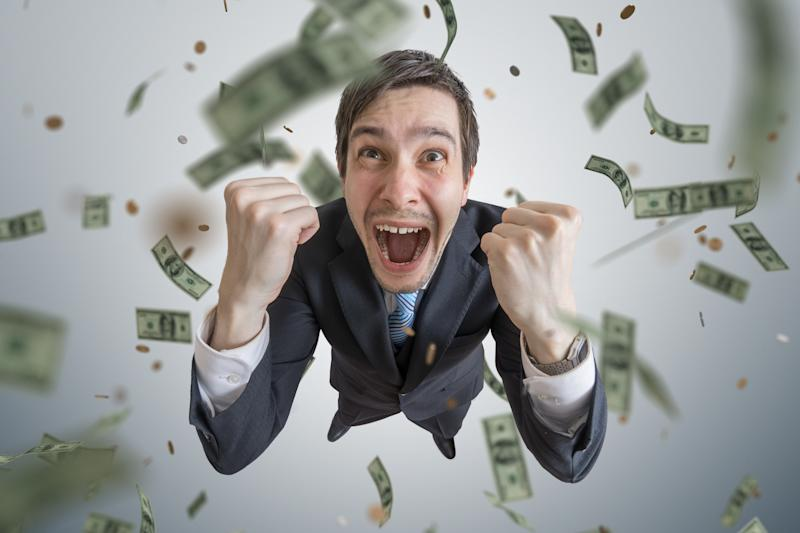 Businessman cheering with money falling.