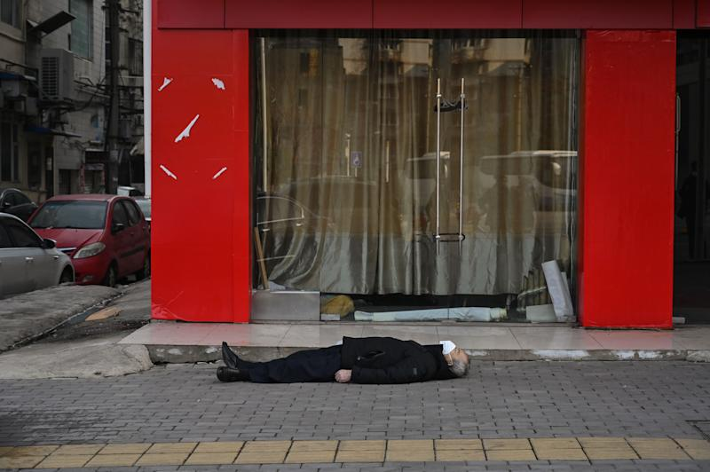 EDITORS NOTE: Graphic content / This photo taken on January 30, 2020 shows an elderly man wearing a facemask lying on the pavement after he collapsed and died along a street near a hospital in Wuhan. - AFP journalists saw the body on January 30, not long before an emergency vehicle arrived carrying police and medical staff in full-body protective suits. The World Health Organization declared a global emergency over the new coronavirus, as China reported on January 31 the death toll had climbed to 213 with nearly 10,000 infections. (Photo by Hector RETAMAL / AFP) / TO GO WITH China-health-virus-death,SCENE by Leo RAMIREZ and Sebastien RICCI (Photo by HECTOR RETAMAL/AFP via Getty Images)