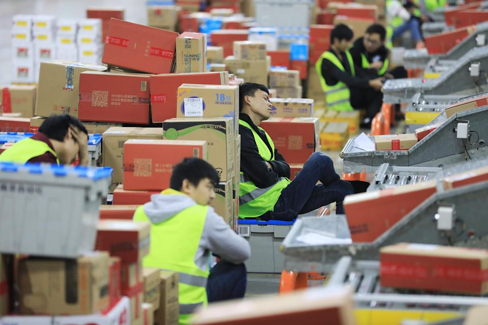 A staff member rests next to a pile of packages at a logistics base of electrical appliance retailer Suning during Alibaba's 11.11 Global Shopping Festival on November 11, 2018 in Nanjing, China. (Photo by VCG via Getty Images)