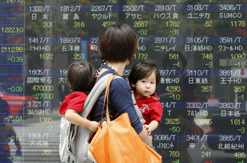 People walk by an electronic stock board of a securities firm in Tokyo, Monday, May 13, 2013. Japan's stock market jumped Monday after global finance leaders gave a seal of approval to the country's stimulus program and refrained from criticizing its weakening effect on the yen. Stocks were mixed elsewhere in Asia. (AP Photo/Koji Sasahara)