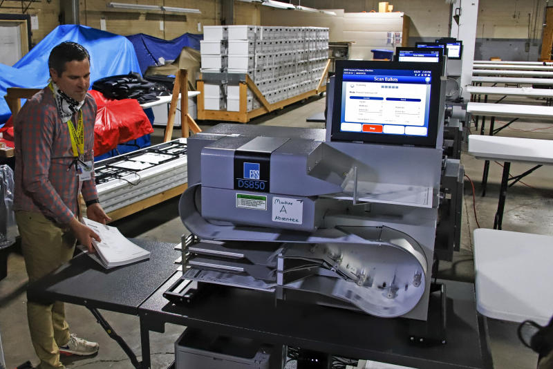 Allegheny County Election Division Deputy Manager Chet Harhut demonstrates a mail-in and absentee ballot counting machine at the Elections warehouse in Pittsburgh on June 1, 2020. (Gene J. Puskar/AP)