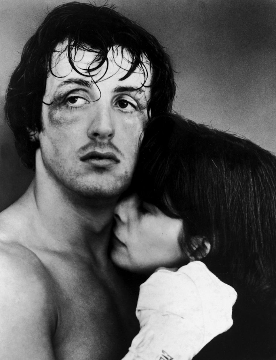 American actors Sylvester Stallone and Talia Shire embrace in a headshot still from the film, 'Rocky,' directed by John G. Avildsen, 1976. Stallone's face is bruised. (Photo by United Artists/Authenticated News/Courtesy of Getty Images)