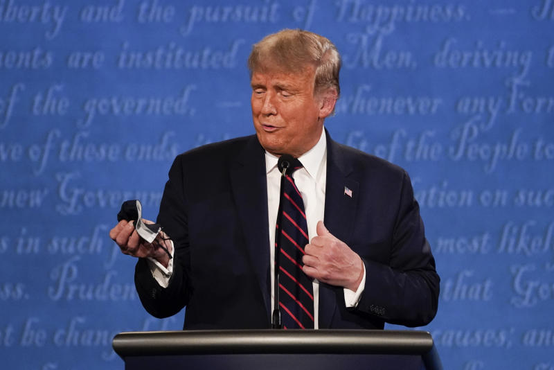 President Donald Trump holds out his face mask during the first presidential debate in Cleveland on Wednesday. (AP Photo/Julio Cortez, File)